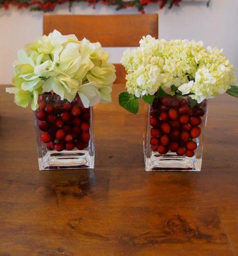 Vázy naplnené červenými brusnicami , ktoré kontrastujú s bielymi kvetmi.